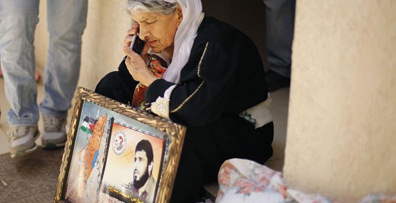 والدة الأسير فارس بارود تحمل صورته قبل وفاتها بأعوام (أرشيف)